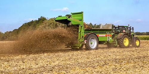 muck spreader Bergmann vertical beater working with a John Deere tractor