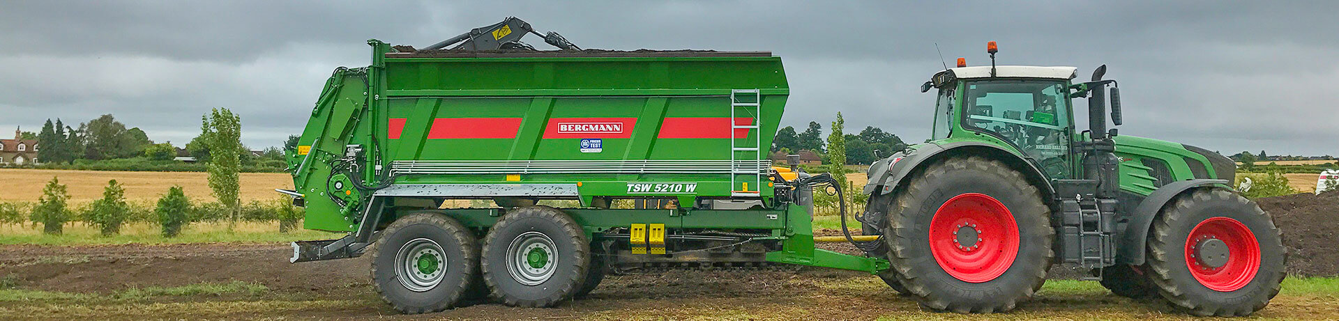 muck spreader being loaded by 360